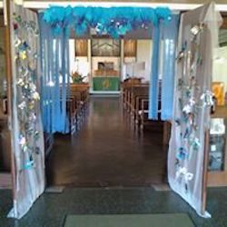 Picture showing the open doors of the church decorated with blue crepe paper